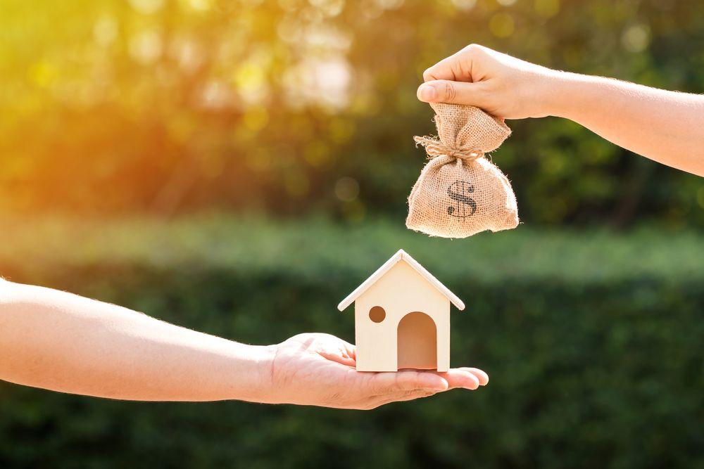 Hand mit einem Hausmodell und eine Hand mit einem Geldsack vor einer Hecke