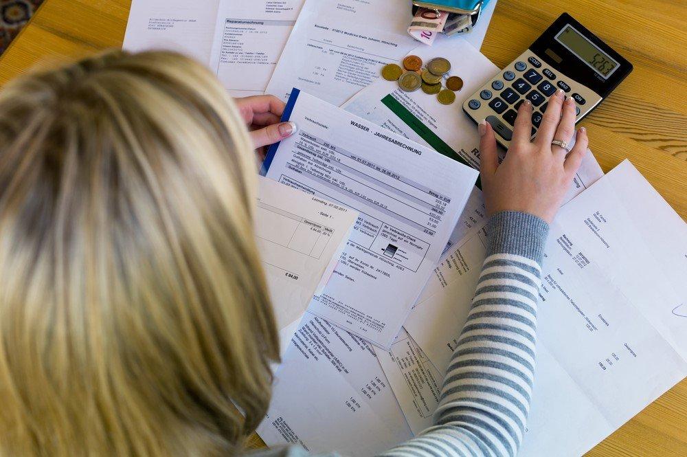 Frau an Schreibtisch mit Rechner und Papieren